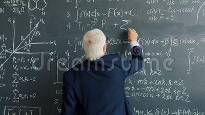 Slow motion of intelligent man in suit writing formulas on blackboard indoors. In college class concentrated on science. People and intelligence concept stock video footage