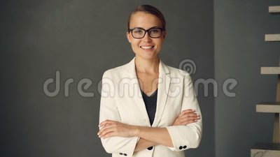 Slow motion portrait of young businesswoman wearing formal clothing and glasses looking at camera and smiling. Confident. People, happy youth and positivity stock video