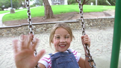 Slow Motion Sequence Of Girl On Swing In Playground Waving. Slow motion sequence of girl in playground swinging towards camera. Shot on Sony FS700 at frame rate stock video