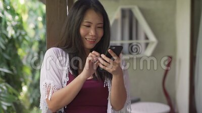 Young beautiful and happy Asian woman in the morning having taking selfie with mobile phone at home terrace or hotel room balcony. Slow motion shot on young stock footage