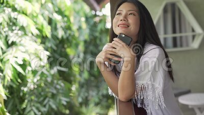 Young beautiful and happy Asian woman in the morning having taking selfie with mobile phone at home terrace or hotel room balcony. Slow motion shot on young stock video footage