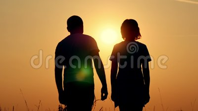 Slow motion silhouette of a happy couple. A guy is hugging a girl against the sunset. Loving man and woman stock video