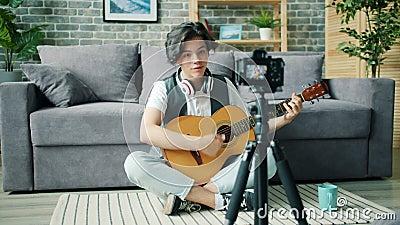 Slow Motion Teenage Blogger spricht für Kamera halten Gitarre zu Hause stock video