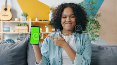 Slow motion of young woman holding smartphone pointing at screen at home. Slow motion of young African American woman holding smartphone pointing at screen stock video footage