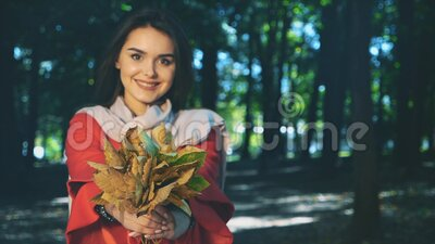 Slowmo. Lovely girl is holding a bunch of autumn leaves. Blurred background. Close up. Copy space. 4K. Concept lovely walk in autumn park. Adorable girl is stock video footage