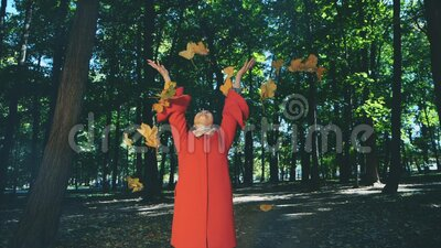 Slowmo. Lovely girl is holding a bunch of autumn leaves and throws them up. Blurred background. Copy space. 4K. Concept lovely walk in autumn park. Adorable stock video