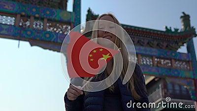 Slowmotion młodej kobiety bloger trzyma małą chińczyk flagi pozycję na Quinmen Main Street centrum handlowym Niedozwolony zdjęcie wideo