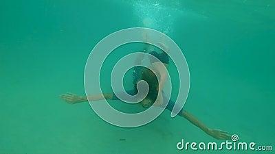 Slowmotion podwodny strzał mężczyzna i jego mały syn ma zabawę w błękitnym morzu zbiory wideo