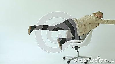 Slowmotion van Gebaarde grappige zakenman hebben pret berijdend op bureaustoel op witte achtergrond stock footage