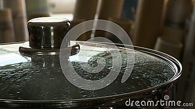 Sluit het deksel van een pot op een kachel. stock footage