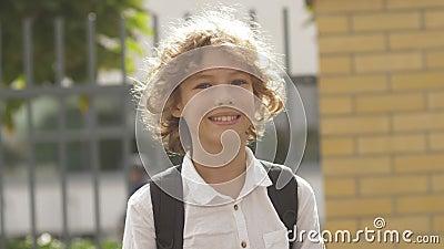 Sluit het portret af van een mooie, aantrekkelijke, krullende haarjongen met rugzak Schoolkind dat kijkt en glimlacht stock video