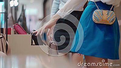 Sluit omhoog De vrouwelijke hand neemt beurzen, zakken en koppelingen van showcase stock video