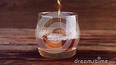 Sluiten van Ice Falling and Pasting Whiskey in Glass stock footage