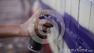 Sluiten van kunstenaars die vuil zijn in verf met spuitnevel en een blauwe gekleurde lijn trekken op een muur van het straatgebou stock videobeelden