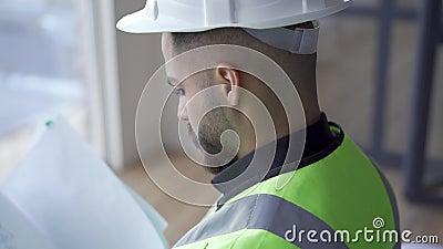 Sluiting van de bebaarde werker in helm en het groene jasje lezen documenten Professionele bouwer met bouwtekeningen in stock video
