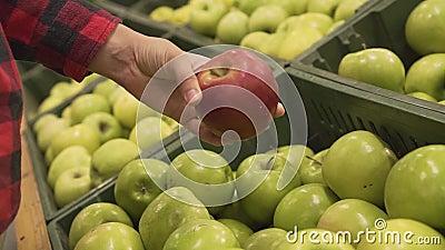 Sluiting van de vrouwelijke hand door rode appel te kiezen tussen groene appels die te koop zijn bij een supermarkt deli stock videobeelden