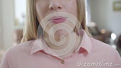 Sluiting van een onherkenbaar blond Kaukasisch meisje dat kauwgom in de mond steekt en glimlacht Onderste gedeelte van het dun vl stock video