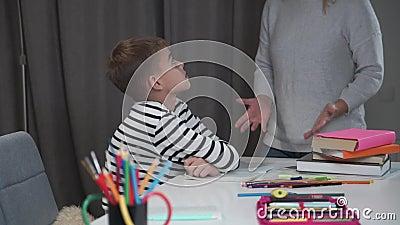 Sluiting van een trieste Kaukasische schooljongen die aan tafel zit terwijl zijn leraar hem de schuld geeft Naughty jongen faalde stock video
