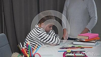 Sluiting van een uitgeputte blanke jongen die aan tafel zit terwijl zijn moeder hem de schuld geeft Naughty zoon weigert te stude stock footage
