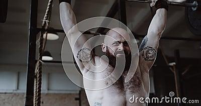 Sluiting van jonge sportman uit de Kaukasus met zwaar gewicht op een kruisstaaf in een grote hardcore gym met trage beweging stock video