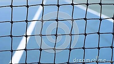 Slutet upp gula tennisbollar slogg det netto på en blå domstol arkivfilmer