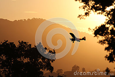 A small airplane landing at sunset.