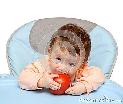 Small baby biting tomato