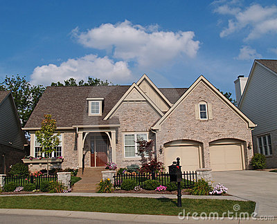 Small Beige Brick Home with Two Car Garage in Fron