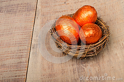 Small bird s nest with orange foil eggs
