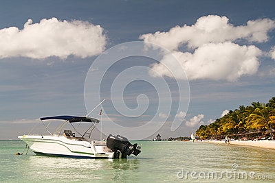 Small boat in front of a tropical beach