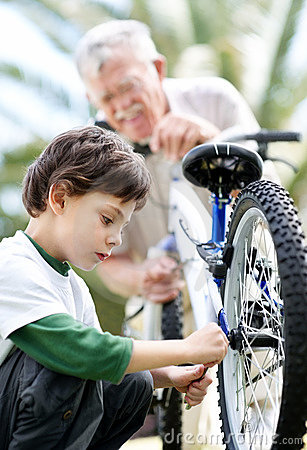 Small boy fixing his bicycle tyre with grandfather
