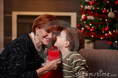 Small boy getting present from grandmother
