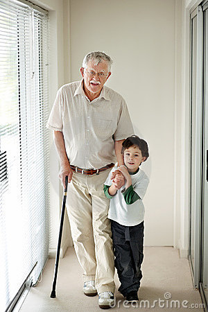 Small boy helping a old man on walking stick