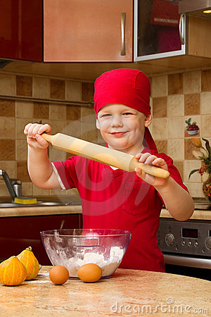 Small boy in kitchen with baking pie