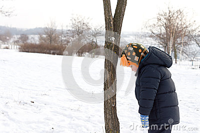 Small boy looking down at the winter snow