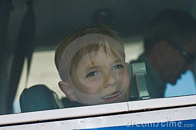 Small boy looks out airplane window