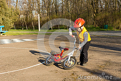 Small boy picking up his bicycle