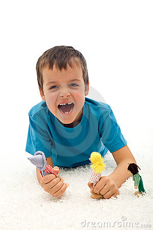 Small boy playing aggressive game with puppets
