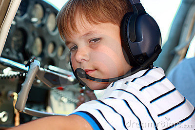 Small boy playing pilot in airplane