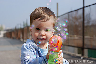Small boy playing with soap bubbles