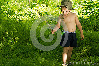 Small boy playing in the woods with a stick