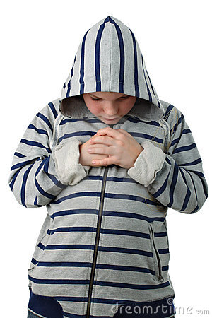 Small boy praying before match isolated on white