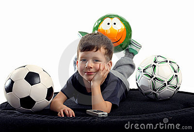 Small boy recreation on sofa with three balls