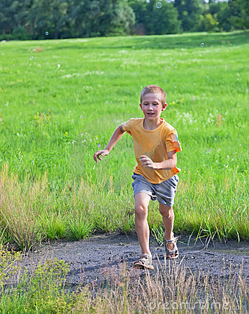Small boy running on green meadow
