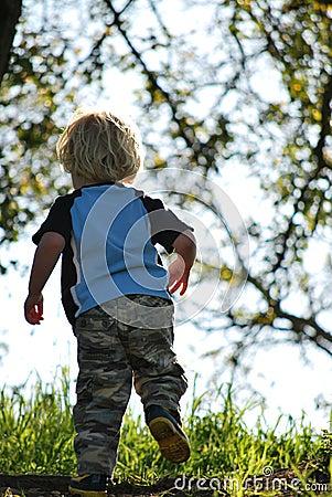 Small boy running up a hill