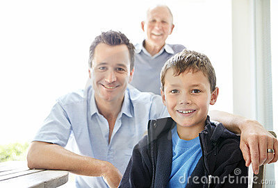 Small boy smiling with his father and grandfather