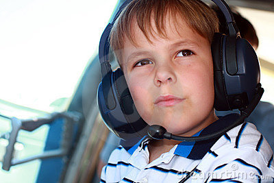 Small boy wearing headset in airplane
