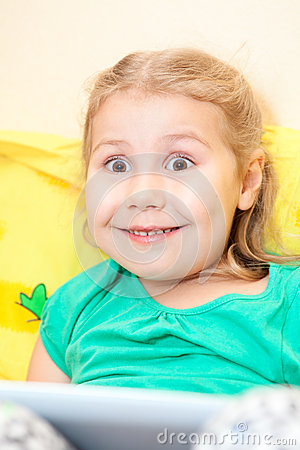 Small girl with funny smile and wide opened eyes sitting with tablet pad