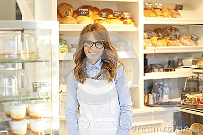 Small coffee shop owner standing in store.