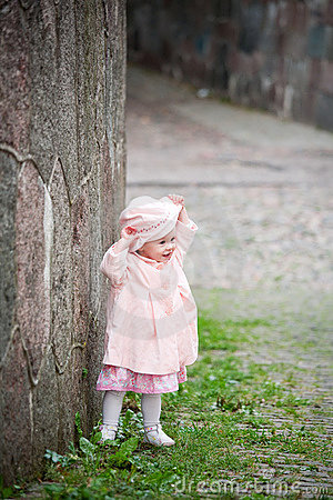 Small cute girl standing near old wall